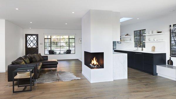 Modern home with living room, ceiling lighting, light hardwood floor, sofa, and corner fireplace. Photo 2 of Vista De la Cumbra
