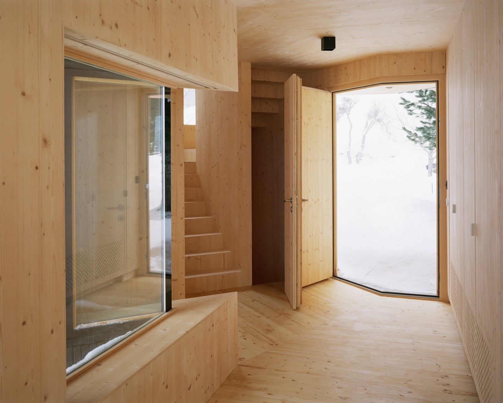 The entryway folds where the two wings meet, creating a V-shaped front door and window.