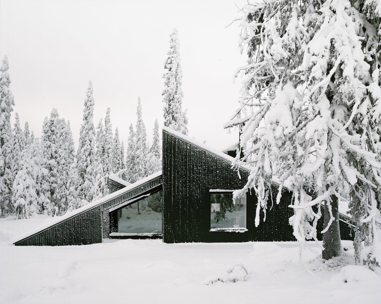 Architect Håkon Matre Aasarød, partner at Oslo-based studio Vardehaugen Architects, led the design of Cabin Vindheim, situated deep in the forest in the alpine landscape near Lillehammer, Norway . The cabin's concept was simple: To create a cabin that is small and sparse yet spatially rich. The 55-quare-meter (592-square-foot) cabin, commissioned by a private client and completed in 2016, comprises a large living room, bedroom, ski room, and small annex with a utility room. It functions off the water and electricity grids. The Vindheim Cabin: Snowbound in Norway - Photo 1 of 18