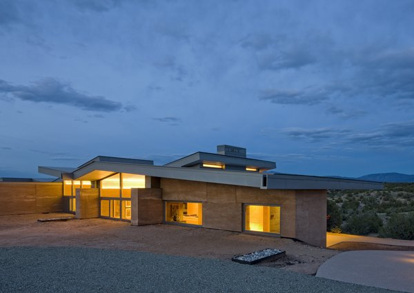 """""""We chose some pretty unique materials for the La Tierra Nueva, informed by Northern New Mexico's traditional building materials, such as mud plastered, site cast adobe and corrugated metal in addition to colors and textures found on the site. The house incorporates zinc siding, selected for its color connection to the site. We used cladding for the walls, and corrugated roofing. The glass was meant to open the home up toe the environment. Finally, the rammed earth building technique had a strong connection to the site itself. """" Graham Hogan, AIA, LEED of Studio GP LLC Photo 15 of La Tierra Nueva modern home"""