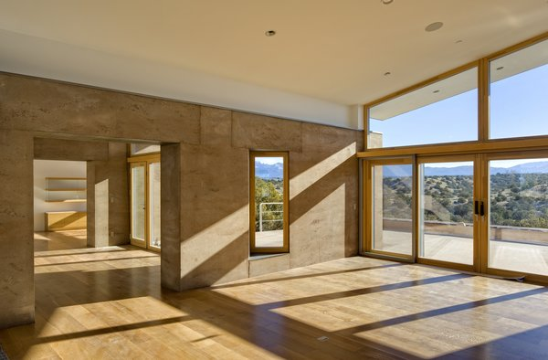 The home's materials and colors were drawn specifically from the site to help it meld into the landscape. It is a custom rammed earth house. Rammed earth is an ancient process originating in the Middle East inspired by a desire to be one with nature. It is a style and building technique that is true to the region, the foundation of the adobe construction that is popular in Santa Fe and surrounding regions. The masonry of the project makes it unique: it was carefully crafted to maximize and adapt to the varying temperatures in the region, allowing for comfortable interior temperatures. Photo  of La Tierra Nueva modern home
