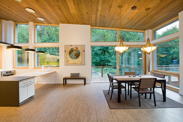 Modern home with windows, casement window type, and wood. Floor-to-ceiling Zola windows in the main living area, gives an expansive view of the surrounding Northwest forest. The tops of these windows reveal the interior cedar clad and the up-swept soffits on the home's exterior, creating a floating ceiling effect. Slatted spruce wood fly-overs break up the vertical areas of the great room and define separate areas that would otherwise feel like an overwhelmingly expansive space. Photo  of Cedar Haus
