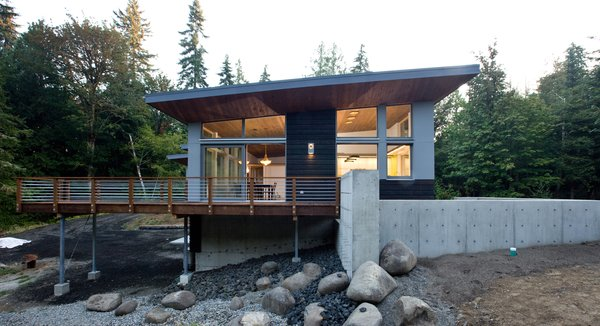 The home seamlessly integrates a floating cedar tongue and groove roof with large sheltering overhangs, clerestory windows, and language of cedar slats for privacy screens and doors inside and out. Photo 6 of Cedar Haus modern home