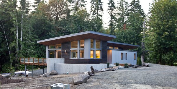 Modern home with windows, wood, and casement window type. Shou Sugi Ban (charred wood) siding creates a resilient and beautifully, natural feel. Zinc-alum metal siding provides a hard contrast to the organic nature of the rest of the exterior. Photo 2 of Cedar Haus