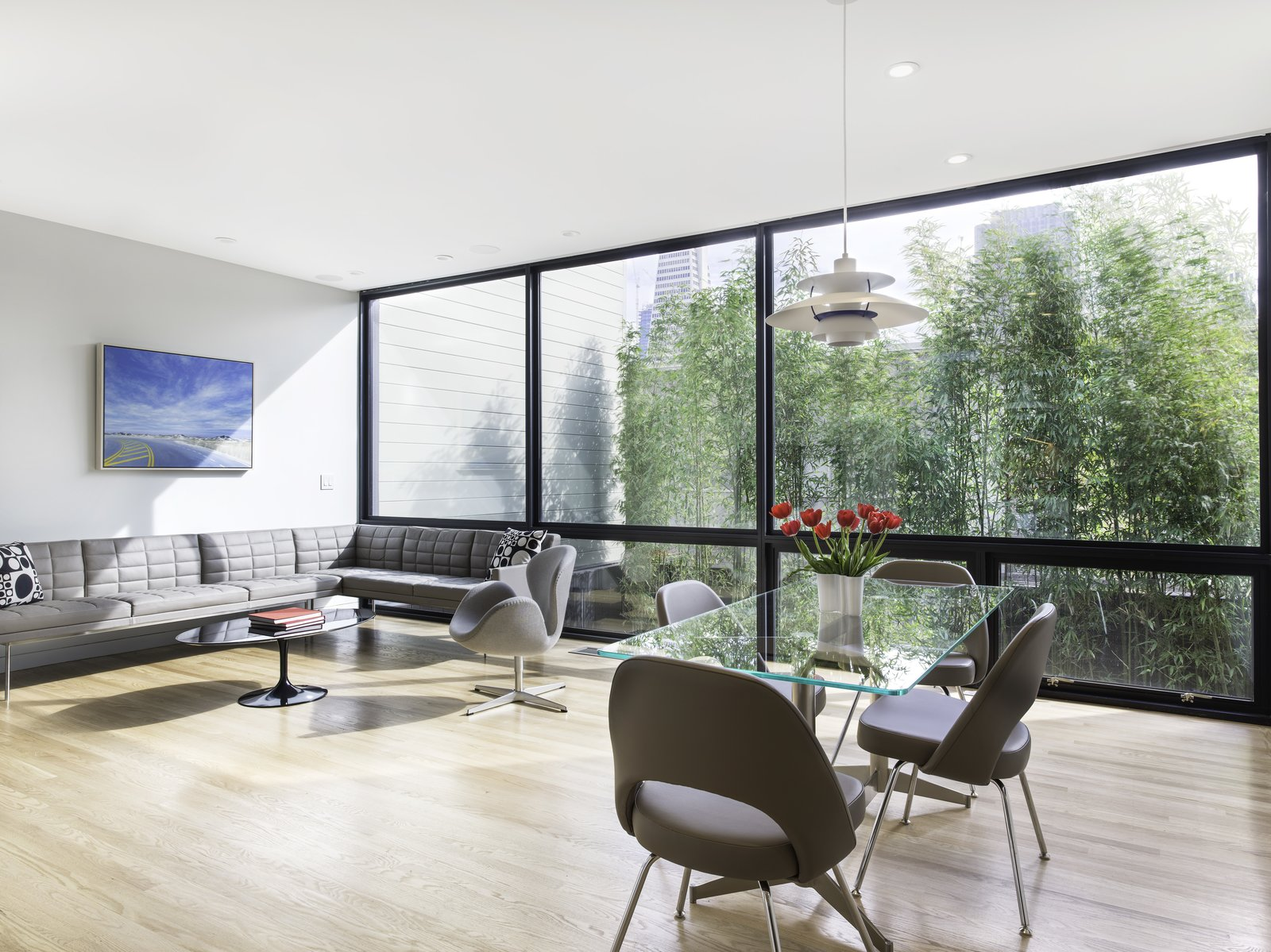 View of the Living-Dining Room with expanse of windows and bamboo hedge beyond for privacy.  Telegraph Hill Periscope by Samaha+Hart Architecture