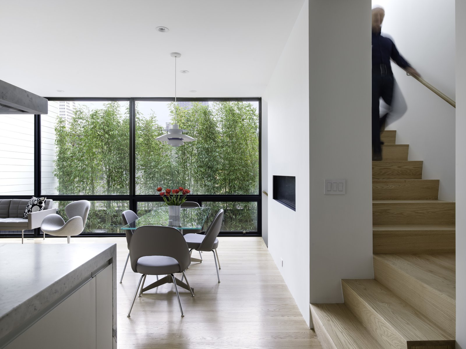 View of the Dining Room from the Kitchen. The Stairway, leading up to the Sun Room and down to the Master Bedroom Level (beyond), wraps around the Fireplace Wall.  Telegraph Hill Periscope by Samaha+Hart Architecture