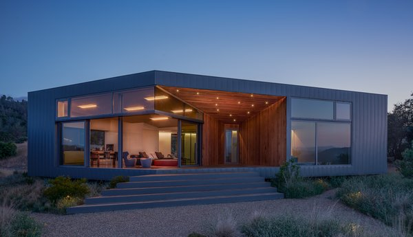 Modern home with outdoor, shrubs, grass, front yard, walkways, and small patio, porch, deck. Exterior, night shot Photo 2 of Lake Berryessa Custom Home
