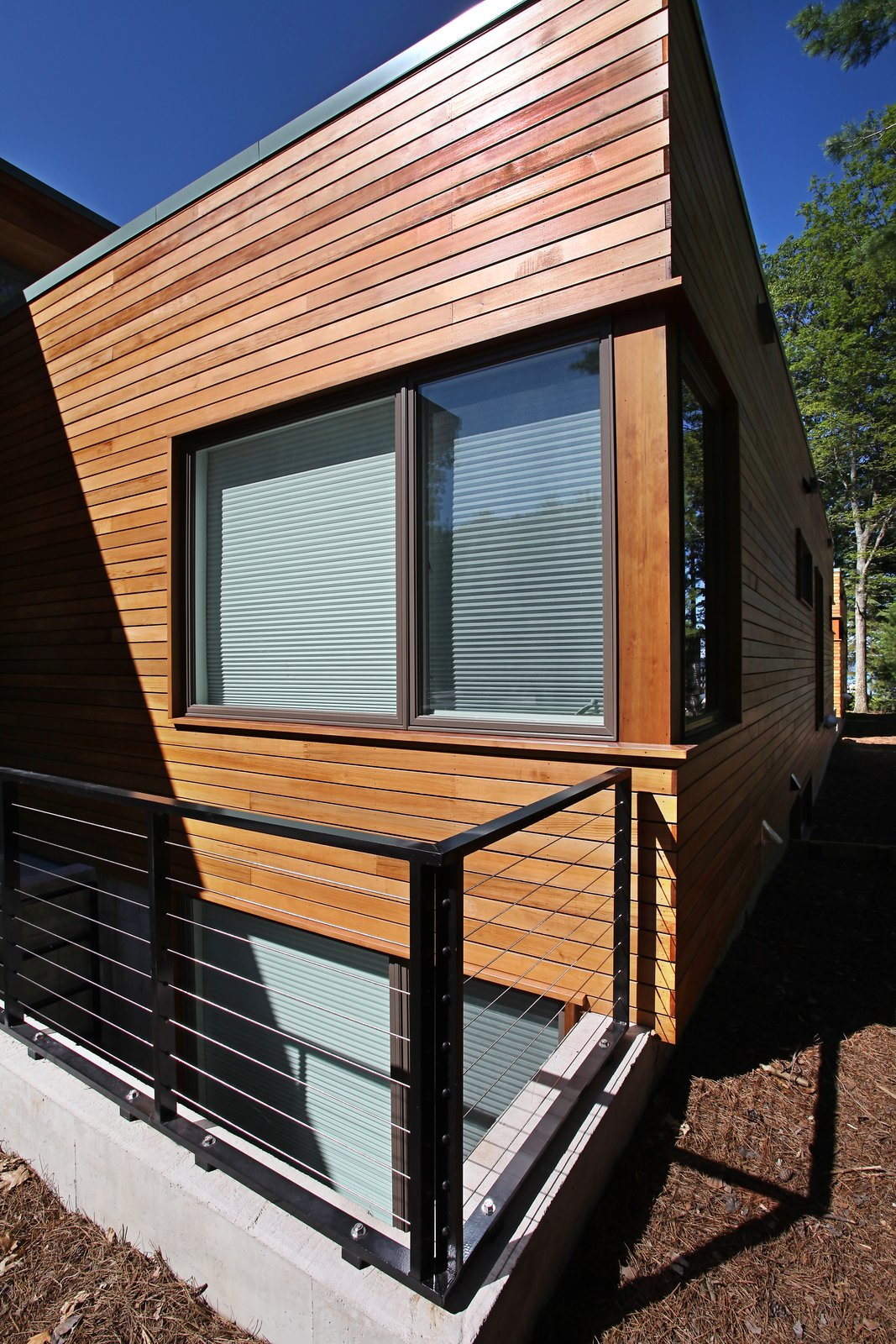 Cedar rain screen and metal guardrail at light well  Higgins Lake House by Jeff Jordan Architects