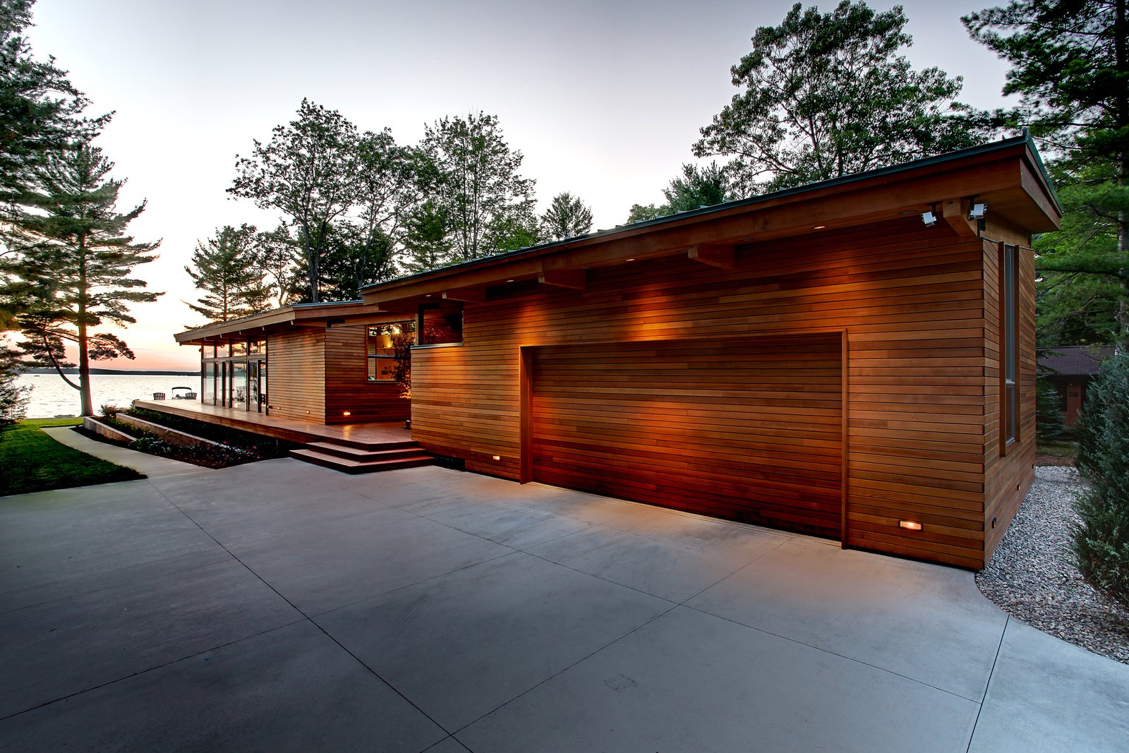 Full south side facade with cedar clad garage door  Higgins Lake House by Jeff Jordan Architects