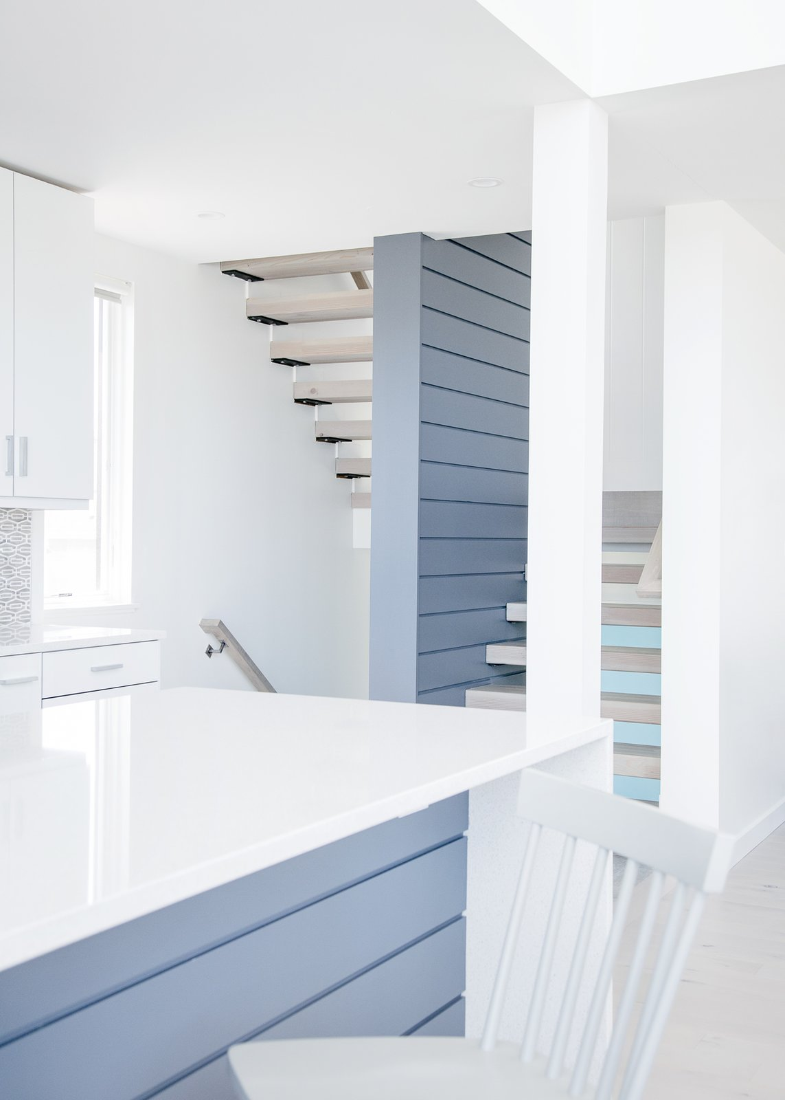 Kitchen and stair Tagged: Kitchen, White Cabinet, Engineered Quartz Counter, Light Hardwood Floor, and Mosaic Tile Backsplashe. Sea Bright House by Jeff Jordan Architects