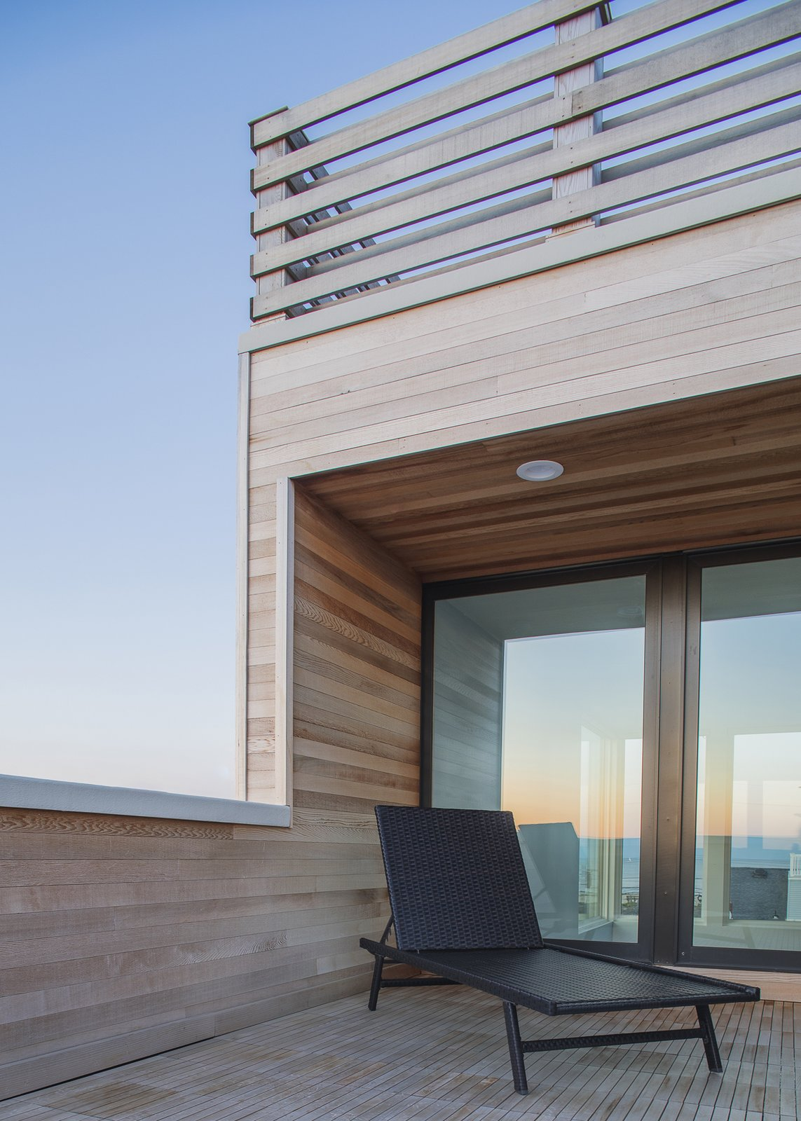 Riverside deck looking through house to ocean at dusk Tagged: Outdoor, Rooftop, Wood Patio, Porch, Deck, Horizontal Fences, Wall, Decking Patio, Porch, Deck, and Wood Fences, Wall.  Sea Bright House by Jeff Jordan Architects
