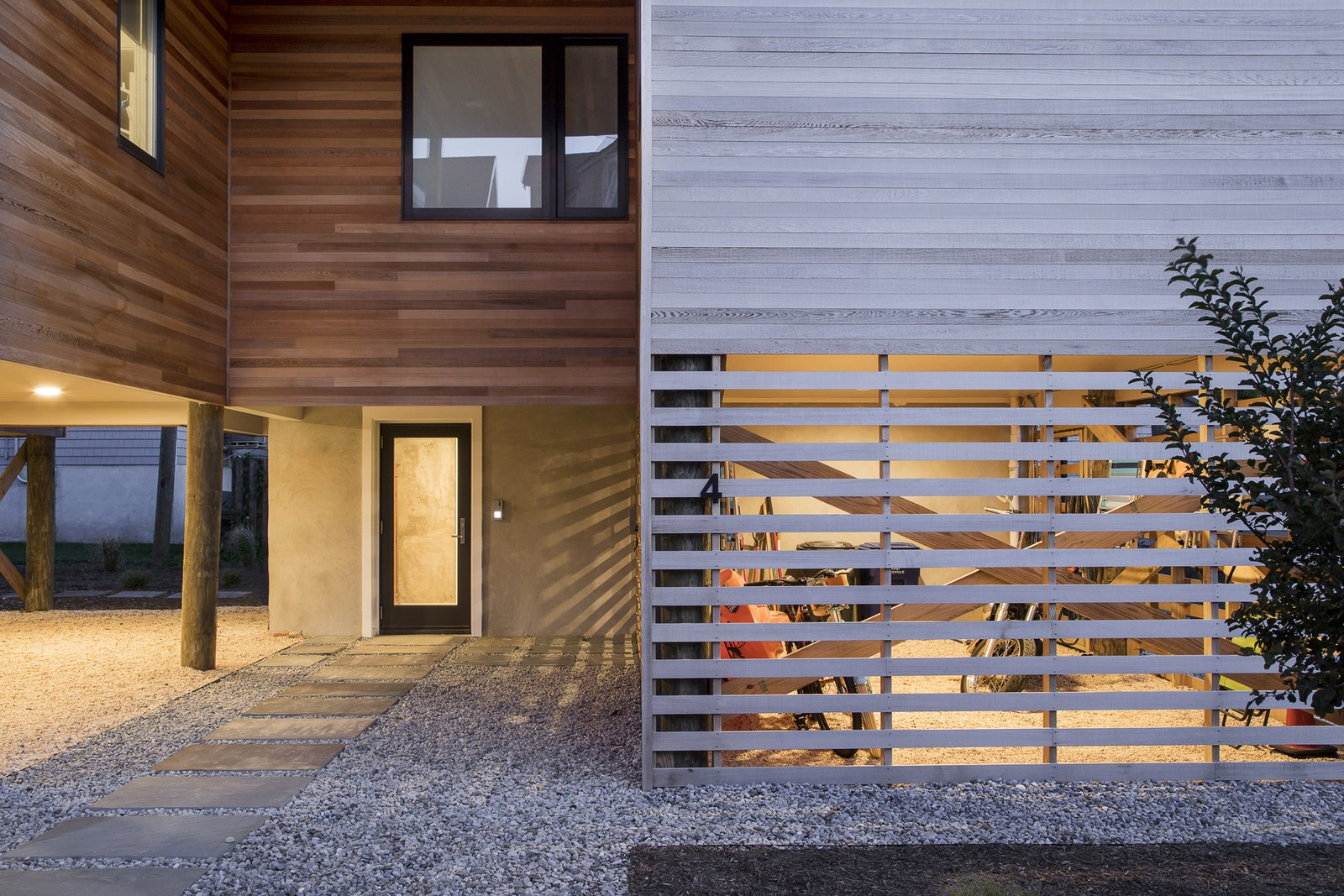 Entryway and screened gear enclosure at dusk Tagged: Outdoor, Front Yard, and Walkways.  Sea Bright House by Jeff Jordan Architects