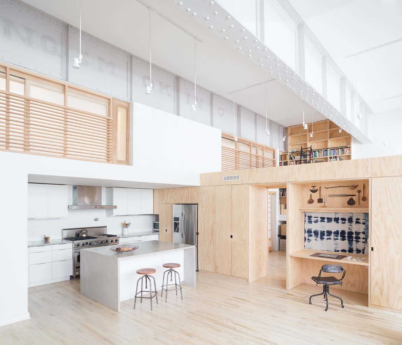 Kitchen and living space looking toward studio and loft bedrooms Tagged: Kitchen, White, Light Hardwood, Concrete, Ceiling, Track, Recessed, Accent, Subway Tile, Refrigerator, Range, and Range Hood.  Best Kitchen White Track Photos from Inspiration