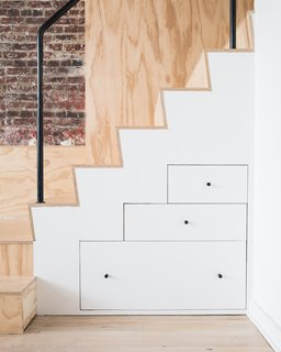 10 Smart and Surprising Under-Stair Design Solutions - Photo 9 of 10 - In the renovation of this former industrial loft for an artist into a studio and living space, built-in drawers under a plywood staircase create visual drama as well as practical storage. By using drawers instead of cabinets, the lower portion of the custom solution is easier to access than if it were cabinets on hinges, and the geometry of the drawers mimics the stair tread.