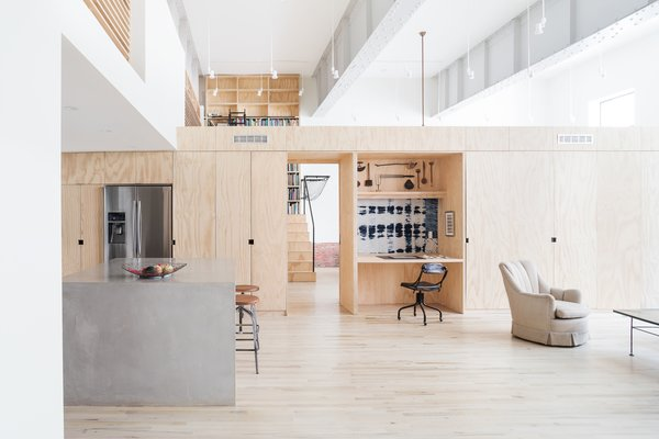 """Modern home with living room, chair, coffee tables, recessed lighting, track lighting, and light hardwood floor. Living space looking toward central organizing """"spine"""" built entirely of plywood Photo  of Wells Fargo Loft"""