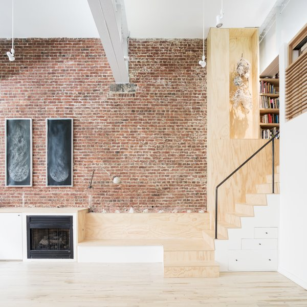 Modern home with living room, track lighting, bench, accent lighting, light hardwood floor, and standard layout fireplace. Plywood stair and bench seat adjacent to fireplace Photo 6 of Wells Fargo Loft