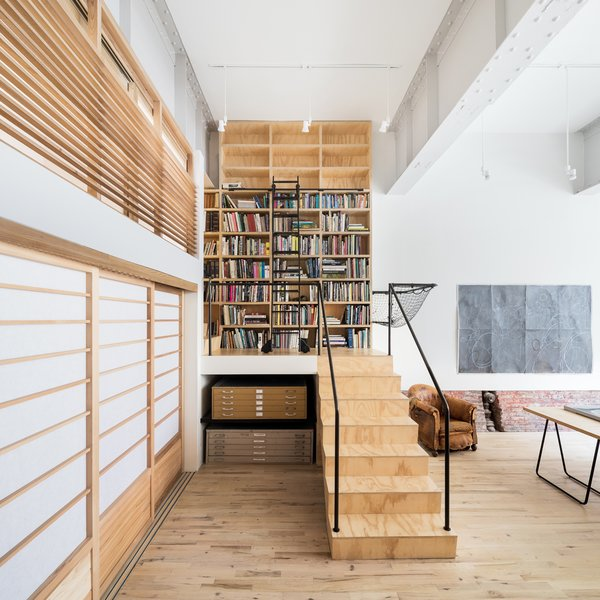 Modern home with office, library, craft room, study, chair, light hardwood floor, bookcase, and shelves. Studio space and stair Photo 9 of Wells Fargo Loft