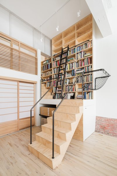 Modern home with office, library, craft room, study, storage, shelves, and light hardwood floor. Stair leading to loft bedroom and library Photo 10 of Wells Fargo Loft