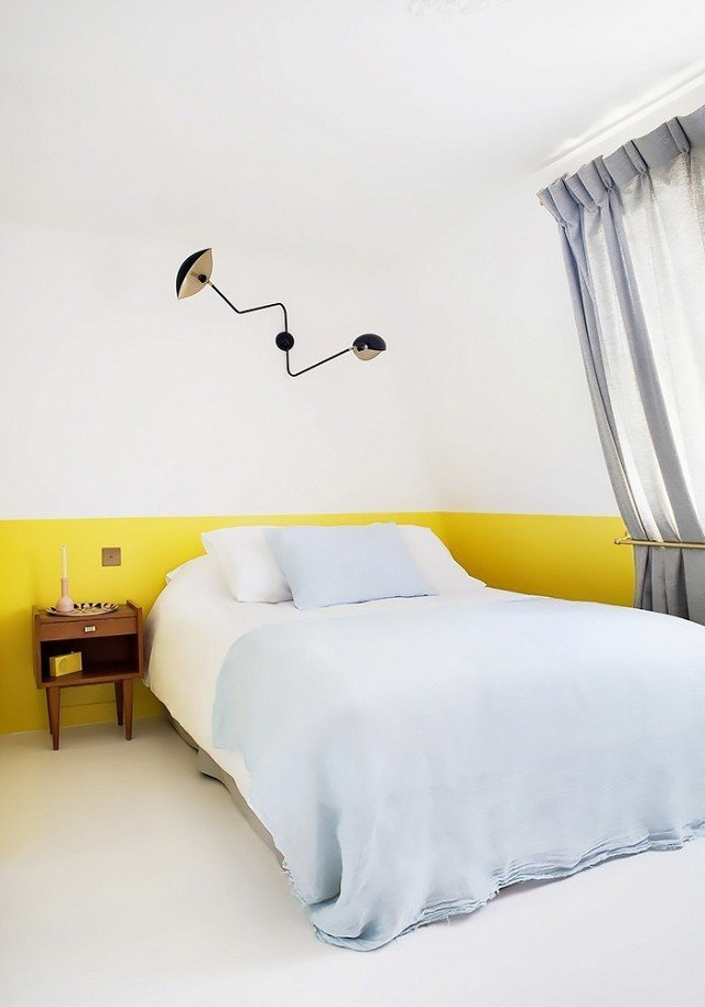 As a paint color, chartreuse can really make a space pop. Playing off soft blue bedding and bright white walls and floor, the yellow hue adds an element of whimsy to a minimal bedroom design.  Photo courtesy of Hotel Henriette  #chartreuse #colorcrush #color #yellow #design #mydomaine  Our Latest Color Crush is Perfect for Summer by MyDomaine
