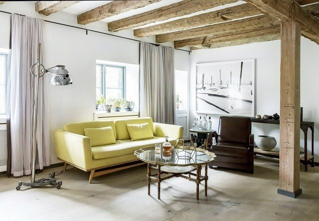 A lemon-lime sofa adds an unexpected slice of optimism to this Scandinavian home design filled with rustic wood and vintage metal.  Photo by Pernille Kaalund for Bo Bedre  #chartreuse #colorcrush #color #yellow #design #mydomaine
