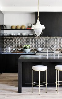 10 Open Kitchen Solutions That Will Get Things Cooking - Photo 10 of 10 - In this kitchen by DISC Interiors, the stark black cabinets and kitchen island are offset by light whitewashed floors and white-and-brass accents. To finish off the look, a patterned ceramic tile backsplash packs a punch.