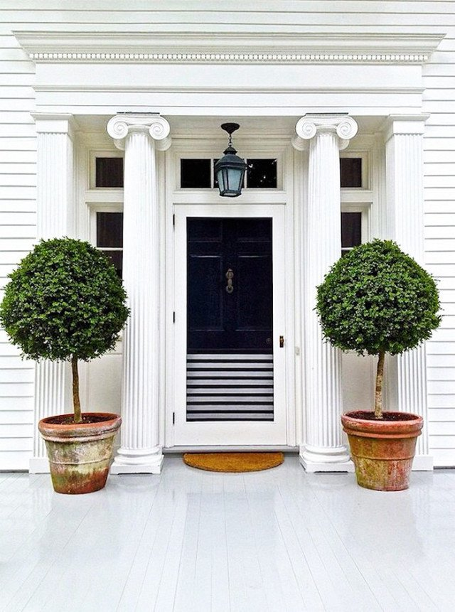 When selecting a front door color, it's always important to be thoughtful of the surrounding colors and finishes, whether they are brick, wood, or even greenery. And if you're looking to integrate a black door with a white frame, there's no reason why can't split the difference with a few classic black-and-white stripes.  Photo 22 of 23 in What's the Best Color to Paint Your Front Door? Your Guide to Finding The One
