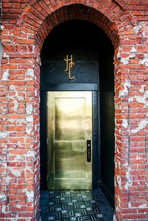 What's the Best Color to Paint Your Front Door? Your Guide to Finding The One - Photo 15 of 22 - This metallic gold door shines bright to welcome guests to L.A.'s Hotel Covell. Against a backdrop of more textural, aged elements like brick walls, it's a chic, smooth, glam touch.