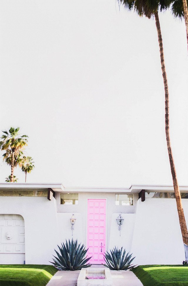 Hello from the outside. This inspiring midcentury pink door is just the right hue for a design style that's retro with a little bit of feminine flair. The bright shade hits the sweet spot between bubblegum and blush for pure Palm Springs perfection.  Photo 4 of 23 in What's the Best Color to Paint Your Front Door? Your Guide to Finding The One