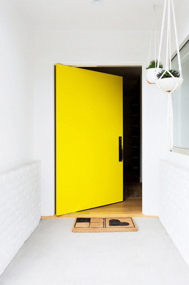 This vibrant, happy shade of yellow invites the sunshine (and sunny vibes) in. That's what makes yellow one of my favorite colors. Accessorized with a simple welcome mat and a few hanging plants, this bright door only requires minimal décor to make a big opening statement.  Photo 2 of 23 in What's the Best Color to Paint Your Front Door? Your Guide to Finding The One