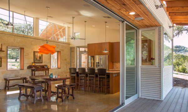 A 24'-wide sliding glass wall in the Great Room opens onto a 14'-deep covered porch. The dining set is a one-off from the 1940's.  Photo  of The Goat Sheds modern home