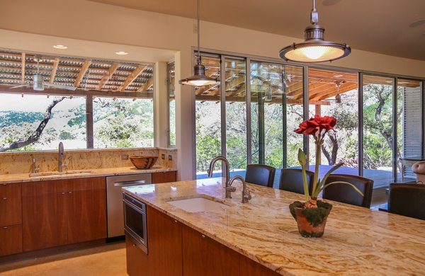 "The kitchen has some of the best views in the house. The sink counter protrudes into the rear porch, with windows on three sides. The owner's refer to it as the ""bridge of the ship.""  Photo 7 of The Goat Sheds modern home"