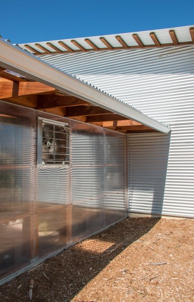 The exterior of the greenhouse is translucent plastic polygal panels screwed to the cedar structure. A thermostat turns on the exhaust fan if it gets too hot during the summer. Photo 11 of The Goat Sheds modern home