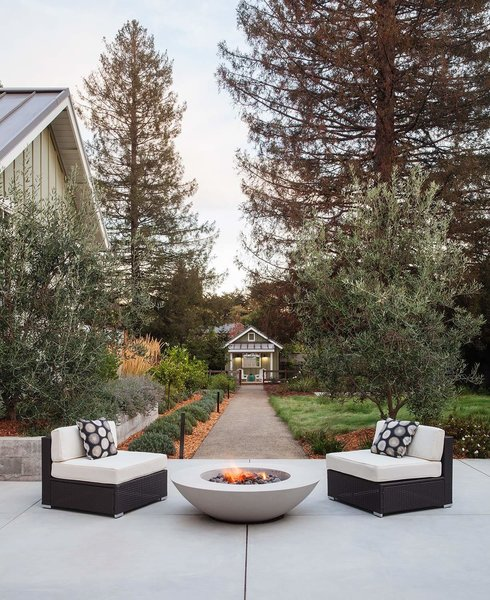 Cozy seating around a fire, with the garden cottage and chicken coop in the distant view.  By Arterra Landscape Architects Photo 9 of Talk of the Neighborhood modern home