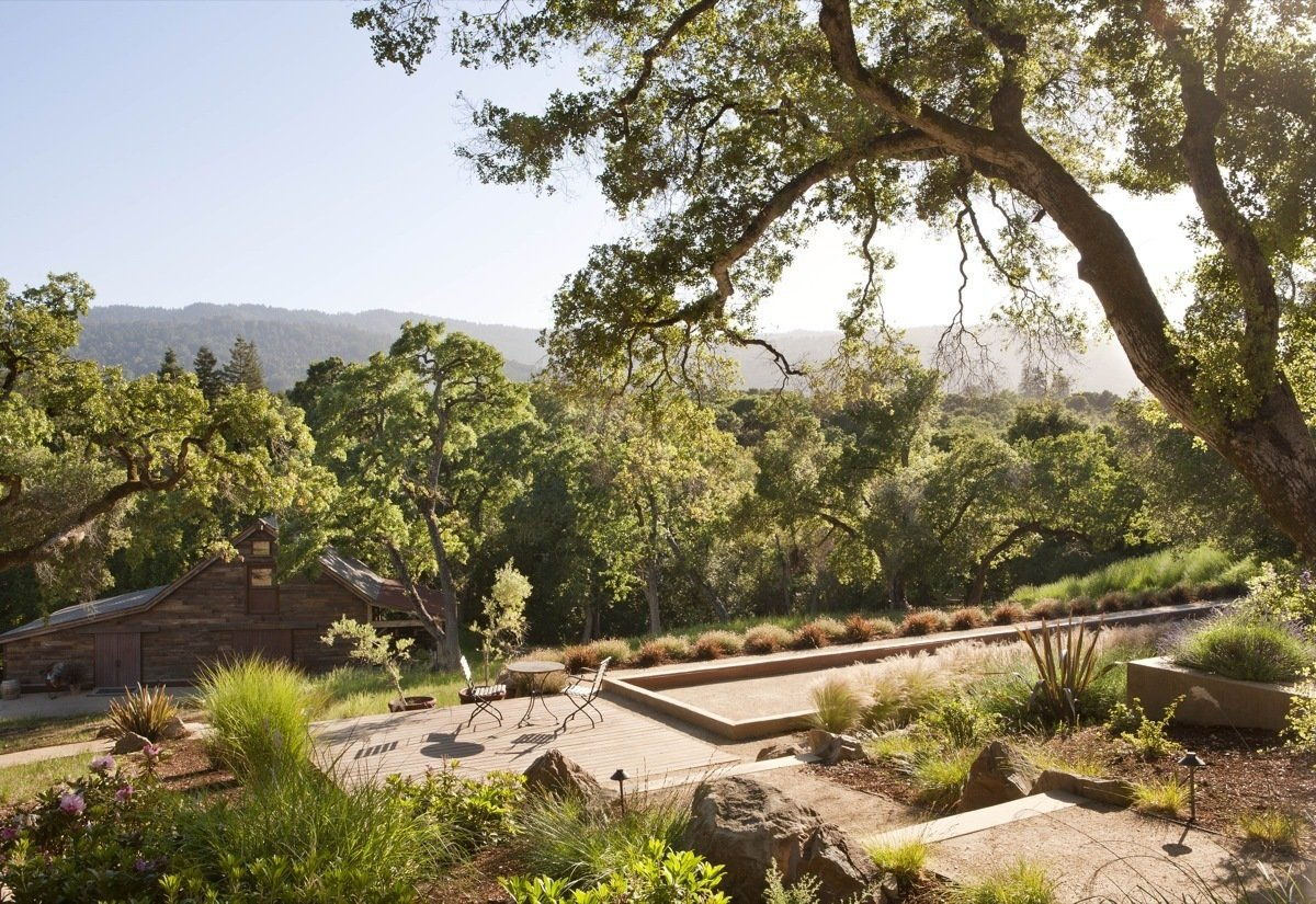 The bocce ball court rests just below the pool and above the barn. It is nestled into the surrounding trees. By Arterra Landscape Architects. Photo by Michele Lee Willson  Homestead on Whiskey Hill by Arterra Landscape Architects