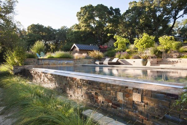 From the bocce court level, the infinity edge of the pool acts as a feature, with water spilling down the stone face. The small barn was reclaimed from the existing agrarian buildings on the property, and now houses the pool mechanical. By Arterra Landscape Architects. Photo by Michele Lee Willson Photo  of Homestead on Whiskey Hill modern home