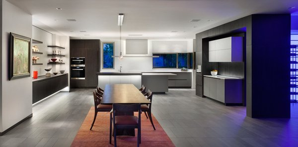 Modern home with kitchen, engineered quartz counter, ceramic tile floor, white cabinet, wood cabinet, accent lighting, recessed lighting, cooktops, wall oven, range hood, wine cooler, and drop in sink. Kitchen and Dining from Patio: the Wine display room is at right. Photo  of the Duncan Residence