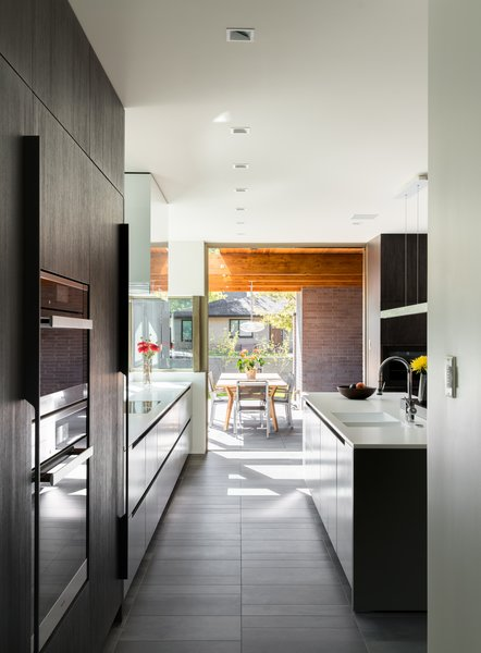 Modern home with kitchen, engineered quartz counter, porcelain tile floor, colorful cabinet, wood cabinet, ceiling lighting, recessed lighting, refrigerator, accent lighting, wall oven, and undermount sink. View from Pantry to East Patio through the Kitchen Photo 6 of the Duncan Residence