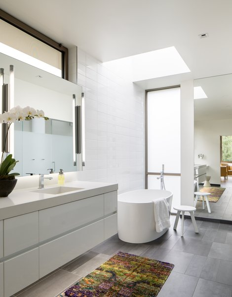 Modern home with bath room, engineered quartz counter, porcelain tile floor, undermount sink, freestanding tub, ceiling lighting, accent lighting, enclosed shower, porcelain tile wall, recessed lighting, and one piece toilet. Master Bathroom Photo 5 of the Duncan Residence