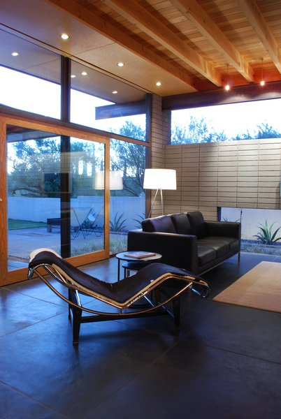 Integral color concrete floors below, and birch soffits above, extend to the exterior breaking the conventional opaque boundary, blurring the line between interior and exterior.  A large custom sliding door can be opened to strengthen the connectivity with the exterior spaces.  Photo 3 of The Silvertree Residence modern home