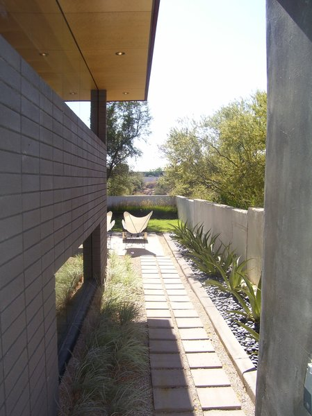 Mullion less butt-jointed glazing was used on the north facade to strengthen the connectivity with the outdoors and provide unfettered views. A large steel beam spans across the space supporting the roof making the roof appear to float over the mullion-less glass below. Photo 5 of The Silvertree Residence modern home