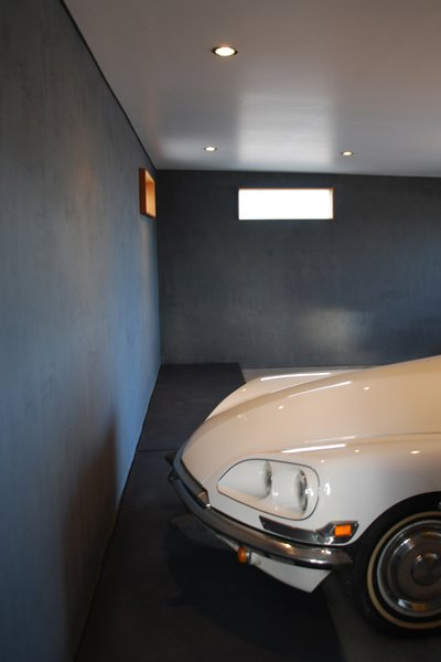 The garage was relocated, creating better access in and out of the garage and allowing the rest of the rear of the house to open to the exterior. The new location buffers the living spaces from the roadway.  The new garage acts as a showplace for the owners beloved restored 1970 Citroen DS. Photo 6 of The Silvertree Residence modern home