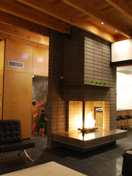A new multi-functional space, and a remodeled kitchen and dining room, all revolve around a new three-sided fireplace. The fireplace is at the nucleus of the space and acts as a focal point while separating the spaces. The fireplace is positioned to open to all of the living spaces as well as the exterior patio. Photo 7 of The Silvertree Residence modern home