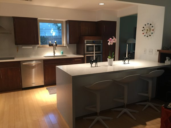 Modern home with kitchen, engineered quartz counter, wood cabinet, light hardwood floor, refrigerator, ceramic tile backsplashe, recessed lighting, wall oven, dishwasher, microwave, cooktops, range hood, and drop in sink. Kitchen Photo 14 of Disco 3332 in Dallas, TX
