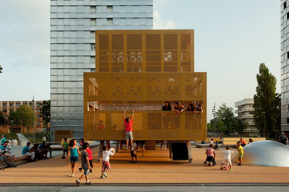 A team of thirty designers and architects developed this perforated playful structure in Bordeaux, France. This chic industriel playground is a modern addition of the Génicart housing community of the 1960s. It revives the spaces with complementary rectangular lines, a sunlit hue, and a compact hub for children to gather and play. 10 Playgrounds With Modern Twists - Photo 3 of 11