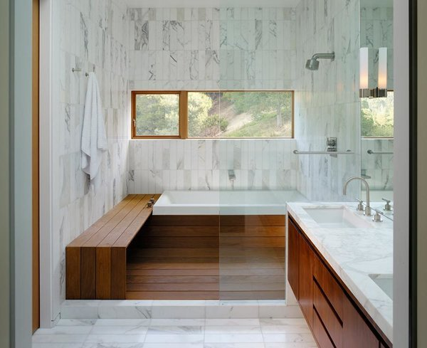 Wood meets white marble in this well-lit bathroom by architect Craig Steely. Contrasting materials make for a warm and serene bathing atmosphere in this Berkeley, California home. Tagged: Bath Room, Enclosed Shower, Marble Wall, Marble Counter, Undermount Sink, and Drop In Tub.  Photo 18 of 20 in 20 Bathrooms With Transformative Tiles