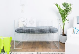 15 Modern and Creative Spaces For Kids - Photo 7 of 15 - Little Crown Interiors inserted a transparent crib into this Los Angeles nursery—along with a clear changing table and side table. Pops of green and blue almost glow in comparison to the transparent surfaces.