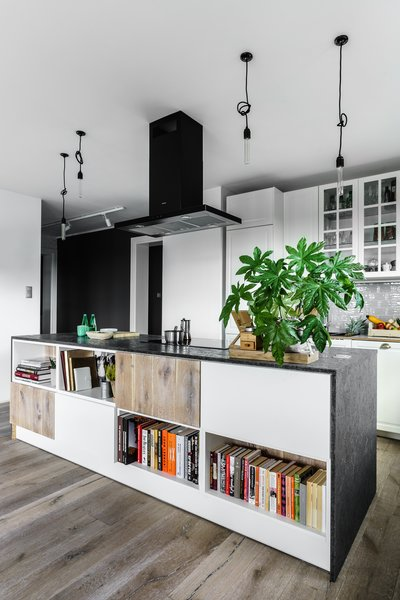 Modern home with kitchen, white cabinet, medium hardwood floor, granite counter, glass tile backsplashe, subway tile backsplashe, pendant lighting, range hood, and cooktops. Photo 6 of Loft in Poland