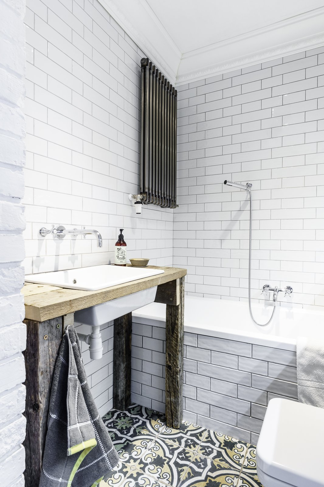 Tagged: Bath Room, Pedestal Sink, Soaking Tub, Wood Counter, Drop In Sink, Subway Tile Wall, and Ceramic Tile Wall.  Loft in Poland by Lucyna Kołodziejska | INTERIORS FACTORY
