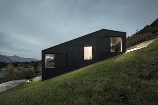 13 Epic Alpine Retreats We're Swooning Over - Photo 1 of 13 - An Austrian vacation home's design references its mountainside setting and expansive views across the valley, and is an exercise in contrasts: its exterior is painted black, but its interiors are light-filled and clad in natural wood.