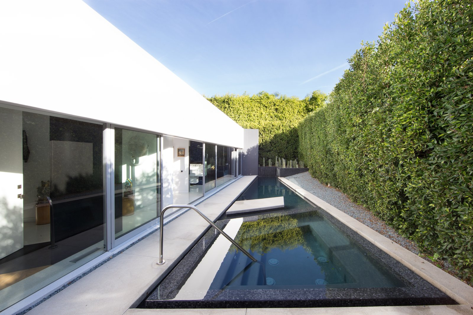 A jewel-like pool and spa fill the narrow master suite garden room.  A New Stage by EPTDESIGN
